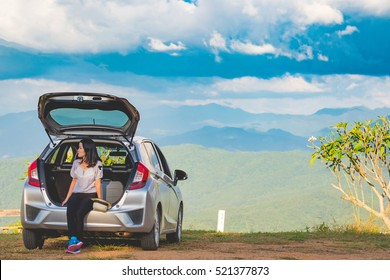 Woman traveler sitting on hatchback car with mountain background in vintage tone
