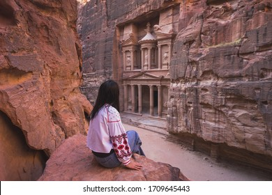 A woman traveler sitting at viewpoint of Petra ancient city looking at the Treasury or Al-khazneh, Jordan, Arab, Asia