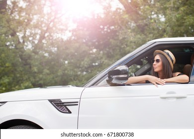 Woman traveler sitting while driving a white SUV