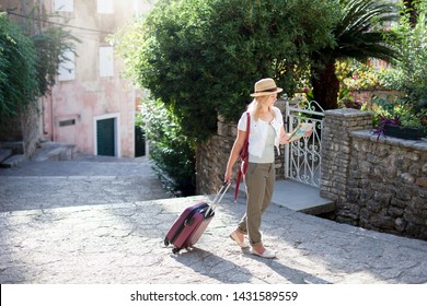 Woman traveler with suitcase looks at city map at town street in Italy. Girl tourist is searching apartment, house. Concept of traveling, summer vacation, female tourism, adventure, trip.