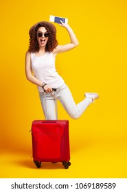 Woman traveler with suitcase on color background