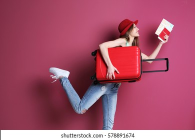 Photo of Woman traveler with suitcase on color background