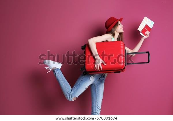 Mujer viajera con maleta en color de fondo