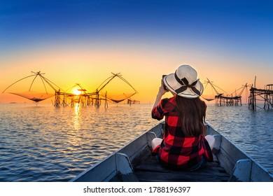 Woman traveler take a photo to fishing dip nets at Pakpra in Phatthalung, Thailand.