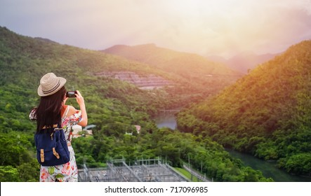 Woman traveler take photo view of dam and mountain with mobile phone.
