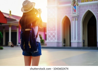 Woman traveler taking photo the church when the sunset.Asia tourist young girl have a good time on vacation. beautiful lady go to travel alone on her holiday.