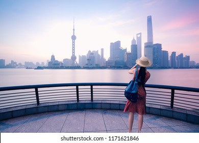 woman traveler taking photo with smart phone at the bund in shanghai, china
