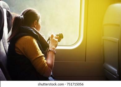 woman traveler taking photos from window seat on train