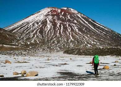 Woman traveler tramping in New Zealand, hiking and walking to the Mount Ngauruhoe, active volcano with red peak, Tongariro Northern Circuit Great Walk, National Park, North Island of New Zealand