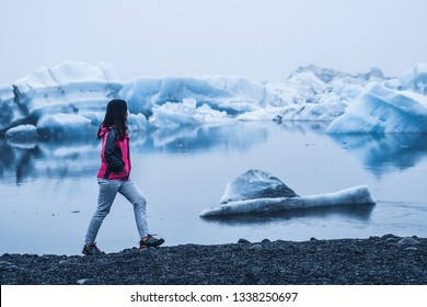Woman traveler travels to Jokulsarlon beautiful glacial lagoon in Iceland. Jokulsarlon is a famous destination in Vatnajokull National Park, southeast Iceland, Europe. Cold winter ice nature.