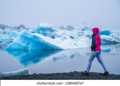 Woman traveler travels to Jokulsarlon beautiful glacial lagoon in Iceland. Jokulsarlon is a famous destination in Vatnajokull National Park, southeast Iceland, Europe. Cold winter ice nature.