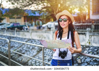 woman traveler using local map and find the way for go to destination.tourist young lady have a good time on vacation. beautiful Asia woman go to travel on holiday.