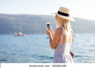 Woman traveler is using mobile phone at summer sea beach. Female tourist is taking photos and smiling. Girl in hat and casual clothes is traveling and enjoying vacation.
