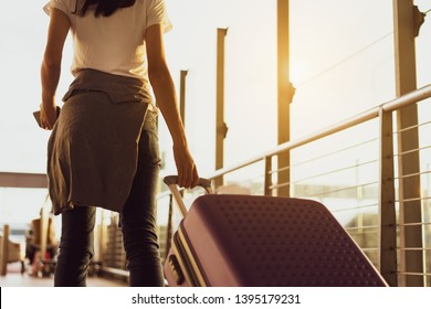 Woman traveler waiting airplane after booking ticket flight at airport with carrying,backpack,suitcase luggage for tranport travel international vacation time in holiday relaxation.