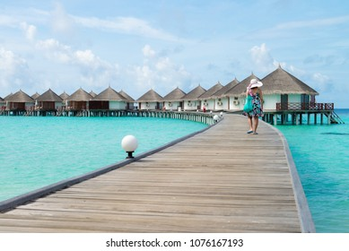 A woman traveler walking alone on wooden planks in the Maldives island on the background of a bungalow on the water and the beauty of the sea with the coral reefs