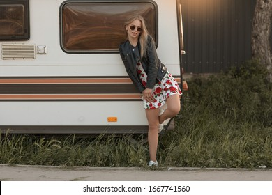 Woman traveler wearing sunglasses in a trip by camper at background in the United States
