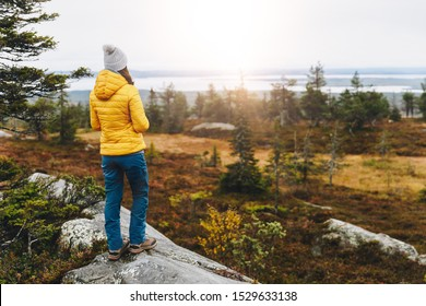 Woman traveler in yellow jacket from back hike in autumn forest in Finland Lapland. Hiking travel and adventure.