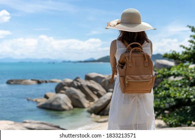 Woman traveling alone with a backpack ,standing back on the rocks, looking at the sea in front. Women travel in the sea and mountains alone.