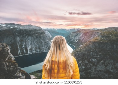 Woman traveling alone enjoying sunset mountains landscape adventure trip lifestyle vacations weekend getaway aerial Norway lake landscape