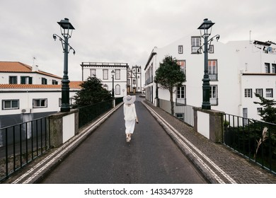 Woman traveling in Azores island walking in city with white buildings