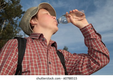 woman traveling with a backpack in the woods, drinking mineral water