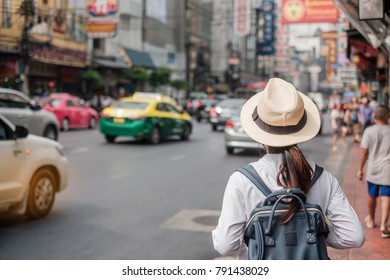 Woman traveling backpacker, Asian traveler standing and walking in China Town street or Yaowarat road, Bangkok landmark and popular for tourist attraction