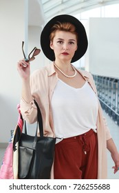 The woman is traveling: elegantly dressed young plump woman in a hat with sunglasses, a shopaholic or a traveler at the airport with a bag