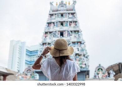 Woman traveling with white dress and hat, happy Asian traveler looking to Sri Mariamman Temple in Chinatown of Singapore. landmark and popular for tourist attractions. Southeast Asia Travel concept
