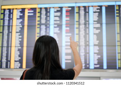 Woman traveller checking flight a departures board at the airport terminal.