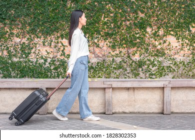 Woman traveller dragging black suitcase luggage bag walking to passenger boarding in airport, Travel concept.