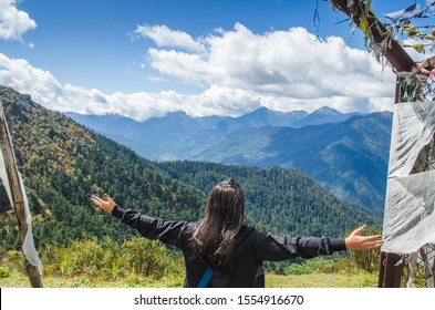 Woman traveller enjoying the picturesque view of the Himalayan mountain range and valleys from the cliff of Chele pass, while trekking on the sunny day