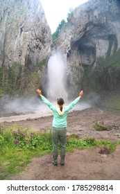 Woman traveller hands up in the air standing near the waterfall in Jili Su Caucasus mountains Russia.