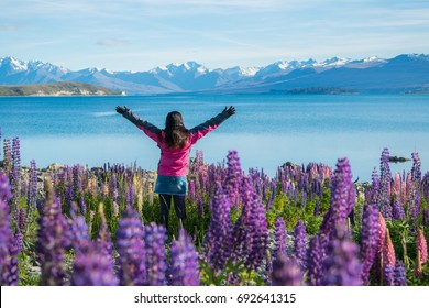 Woman traveller at lake Tekapo, New Zealand. Lupin flower at lake Tekapo hit full bloom in summer season.