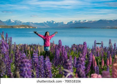 Woman traveller at lake Tekapo, New Zealand. Lupin flower at lake Tekapo hit full bloom in December, summer season of New Zealand.