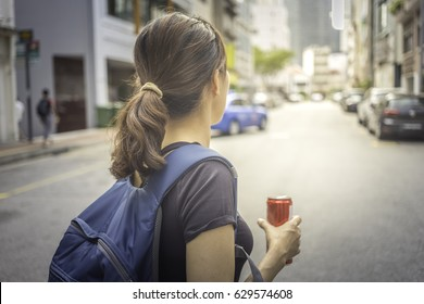 woman traveller on city street with backpack and can drink in hand