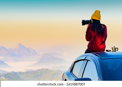 Woman traveller photographer sitting to takes a photo shot on her owns roof of the car with scenery view of the mountain and mist morning in background