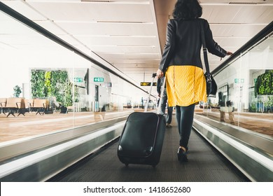 Woman traveller with travel suitcase or luggage walking in airport terminal walkway for vacation travel abroad. concept of travel around world, tourism. Brunette in yellow skirt goes on escalator.