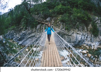 A woman travels alone in picturesque places. A girl with a backpack crosses the canyon on a suspension bridge. A woman walks along a mountain trail alone. Walk through the woods.