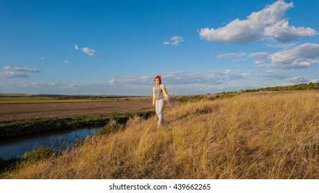 Woman travels on a background of field and river