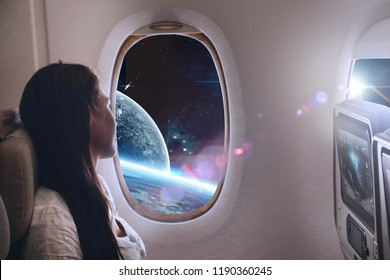 A woman travels in the universe inside an airplane or space shuttle e. look out the window and see the planets and the stars. Concept of: dreams, travels, future.