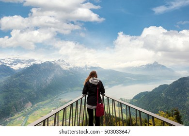 Woman traverler looking aerial view of the city district and Interlaken from viewpoint at Harder Kulm in Interlaken, Bern, Switzerland.