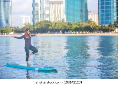 Woman in tree pose loving SUP Yoga practice sunrise in Waikiki