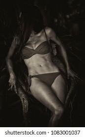 Woman in tree roots, body in swimsuit, scary,sensual,dark,sepia, film grain
