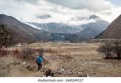 A woman trekker heading to Samagau valley on Manaslu circuit with view of Mount Manaslu range 8 156 meters. Himalayas, stone buildings in village, at Manaslu Glacier in Gorkha District in Nepal