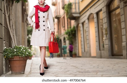 Woman with the trench coat, red scarf and purse in the town Autumn fall winter fashion image.