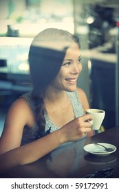 Woman at trendy cafe drinking coffee. Young beautiful Caucasian / Asian model. Reflections from windows. Image cross processed.