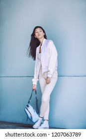 Woman Trendy Fashion. Attractive sporty asian girl in full length with elegant hairstyle and perfect soft colorful makeup. Female with perfect slim body in sport trendy clothes against fancy wall on