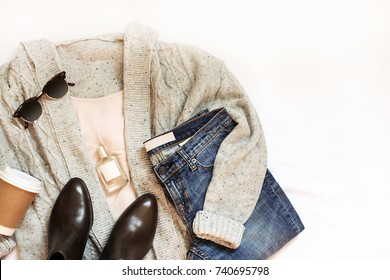 Woman trendy fashion clothes gray knit cardigan, pastel shirt, blue jeans with boots and accessories on white bed sheet, flat lay, top view.
