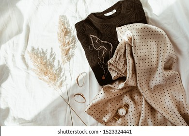 Woman trendy fashion clothes on white linen bed. Flat lay, top view. Black sweater, silk skirt with polka dots, gold necklace, watch, earrings, reeds. Feminine french style concept.