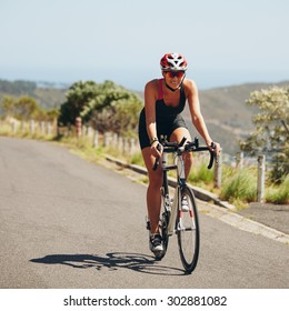 Woman triathlon athlete cyclist down hill on country road. Young woman riding bicycle on open road, practicing for triathlon competition.
